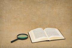 La loupe et le livre ouvert se trouvent contre une toile brune Images stock
