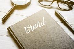 La loupe, les lunettes, le stylo et le carnet écrits avec la MARQUE sur le fond en bois blanc avec le soleil évasent photo stock
