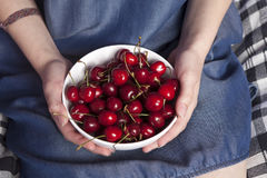 La loza con las cerezas en manos de la mujer fotografía de archivo