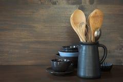 La loza, el clayware, los utensilios oscuros y otra diversa materia en el tablero de la mesa de madera Todavía de la cocina vida  fotografía de archivo