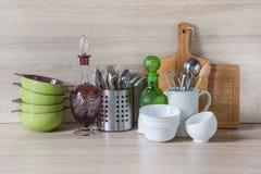 La loza, el vajilla, los utensilios y otra diversa materia en tablero de madera Todavía de la cocina vida como fondo para el dise foto de archivo libre de regalías