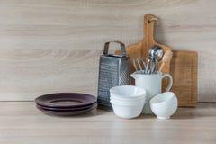 La loza, el vajilla, los utensilios y otra diversa materia en tablero de madera Todavía de la cocina vida como fondo para el dise fotografía de archivo