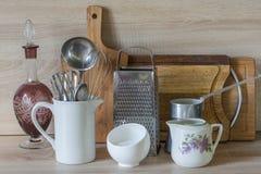 La loza, el vajilla, los utensilios y otra diversa materia en tablero de madera Todavía de la cocina vida como fondo para el dise imágenes de archivo libres de regalías