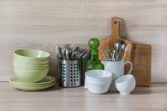 La loza, el vajilla, los utensilios y otra diversa materia en tablero de madera Todavía de la cocina vida como fondo para el dise fotos de archivo libres de regalías