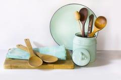La loza, el vajilla, los utensilios y el otro diversos blanco y materia de la turquesa en tablero blanco Todavía de la cocina vid fotos de archivo