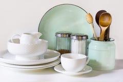 La loza, el vajilla, los utensilios y el otro diversos blanco y materia de la turquesa en tablero blanco Todavía de la cocina vid fotografía de archivo libre de regalías