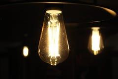 La luce accende la luminosità di oscurità tre lampadine fotografia stock