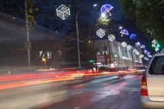 La luce ad alta velocità e vaga delle automobili trascina in via del centro di notte Tracce del semaforo dentro in città Natale i Immagini Stock
