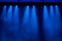 La luce blu dai riflettori attraverso il fumo nel teatro durante la prestazione Fotografie Stock