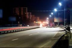 La luce dell'automobile trascina sulla via, fondo della via di notte Foto lunga di esposizione Fotografia Stock