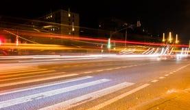 La luce dell'automobile trascina sulla via vicino al ponte della strada, la gente che cammina nel moto veloce, fondo della via di Immagini Stock Libere da Diritti
