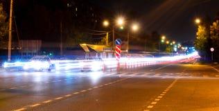 La luce dell'automobile trascina sulla via vicino al ponte della strada, la gente che cammina nel moto veloce, fondo della via di Immagini Stock