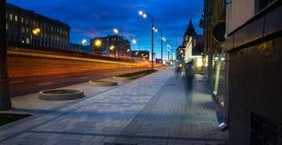 La luce dell'automobile trascina sulla via vicino al ponte della strada, la gente che cammina nel moto veloce, fondo della via di Fotografie Stock Libere da Diritti