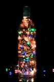 La luce della bottiglia di vetro con il rosa giallo arancione di verde blu di natale si accende sopra fondo nero Immagine Stock
