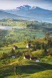 La luce di mattina si trova sulle colline di un villaggio della molla sotto Hoverla immagini stock