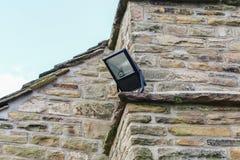 La luce di sicurezza domestica ha montato sull'angolo di un cotta di pietra rurale immagini stock