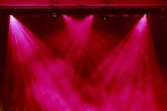 La luce rossa dai riflettori attraverso il fumo al teatro durante la prestazione Immagini Stock Libere da Diritti