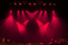 La luce rossa dai riflettori attraverso il fumo al teatro durante la prestazione Immagine Stock