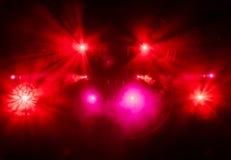 La luce rossa dai riflettori attraverso il fumo al teatro durante la prestazione Fotografie Stock
