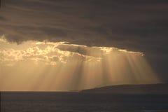 La luce solare attraverso le nuvole illumina il mare immagine stock