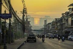 La luce solare di primo mattino che splende sulle costruzioni e sulle automobili sulla strada alla città di Bangyai di Nonthaburi fotografia stock libera da diritti