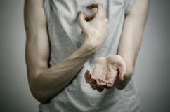 La lucha contra las drogas y tema de la drogadicción: adicto sucio flaco que lleva a cabo una jeringuilla con una droga y el cora Imagen de archivo