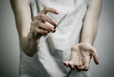 La lucha contra las drogas y tema de la drogadicción: adicto sucio flaco que lleva a cabo una jeringuilla con una droga y el cora Imagen de archivo libre de regalías