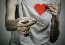La lucha contra las drogas y tema de la drogadicción: adicto sucio flaco que lleva a cabo una jeringuilla con una droga y el cora Fotografía de archivo libre de regalías
