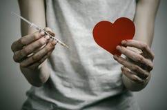 La lucha contra las drogas y tema de la drogadicción: adicto sucio flaco que lleva a cabo una jeringuilla con una droga y el cora Imágenes de archivo libres de regalías