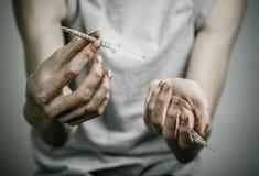 La lucha contra las drogas y tema de la drogadicción: adicto sucio flaco que lleva a cabo una jeringuilla con una droga y el cora Fotografía de archivo