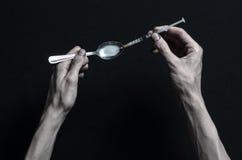La lucha contra las drogas y tema de la drogadicción: las mentiras del adicto a la mano en una tabla oscura y alrededor de ella s imagen de archivo libre de regalías