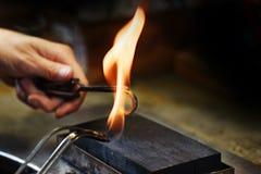 La lueur de mains d'orfèvre un anneau d'or dans une flamme de gaz, se ferment avec Images stock