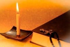 La lumière d'or et la bible toujours de bougie de la vie réservent sur d'or brouillées Image stock