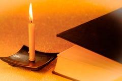 La lumière d'or et la bible toujours de bougie de la vie réservent sur d'or brouillées Photographie stock libre de droits