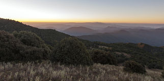 La lumière de matin monte à travers des sommets de montagne photographie stock libre de droits