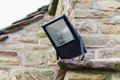 La lumière de sécurité à la maison a monté sur le coin d'un cotta en pierre rural Image libre de droits