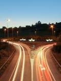 La lumière de véhicule traîne sur les bateaux de route et de papier dans un rond point Photographie stock libre de droits