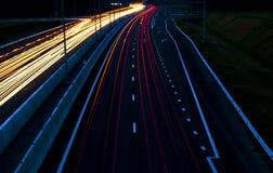La lumière de voitures traîne sur une route incurvée la nuit Traînées du trafic de nuit Tache floue de mouvement Route urbaine de photographie stock libre de droits