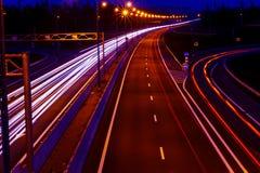 La lumière de voitures traîne sur une route incurvée la nuit Traînées du trafic de nuit Tache floue de mouvement Route urbaine de images libres de droits