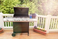 La lumière du jour lumineuse sur la plate-forme avec le cuiseur ouvert de barbecue et mis en bouteille soit images libres de droits