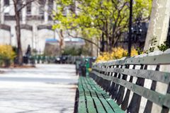 La lumière du soleil brille sur le banc de parc vide à Manhattan, New York City Image stock