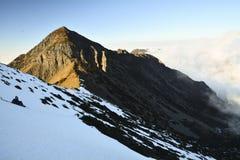 La lumière du soleil d'or sur l'arête couverte de neige Photographie stock libre de droits
