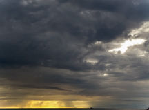La lumière du soleil et les nuages de pluie foncés regardent impressionnants la plage Photos stock