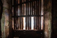 La lumière du soleil pénètre la fenêtre piétinée dans la vieille chambre noire photos stock