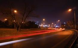 La lumière rouge de voiture traîne sur une route la nuit Images stock