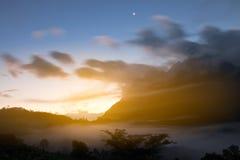 La luna è su durante il tramonto, l'alta montagna di vista e la nebbia del mare Fotografie Stock