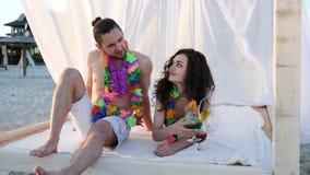 La luna de miel, gente joven en guirnaldas coloridas toma el sol en casa de planta baja en la playa, contraluz, par de amantes en