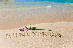 La luna di miele dell'iscrizione ed è aumentato sul litorale di mare Fotografie Stock Libere da Diritti