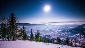 la luna 8K y las estrellas sobre las montañas del invierno aterrizan, lapso de tiempo almacen de metraje de vídeo