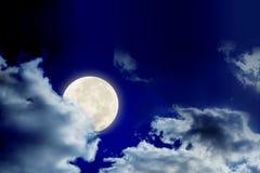 La Luna Llena y las nubes grandes en cielo oscuro, la luna está detrás de la nube como fondo Fotos de archivo libres de regalías